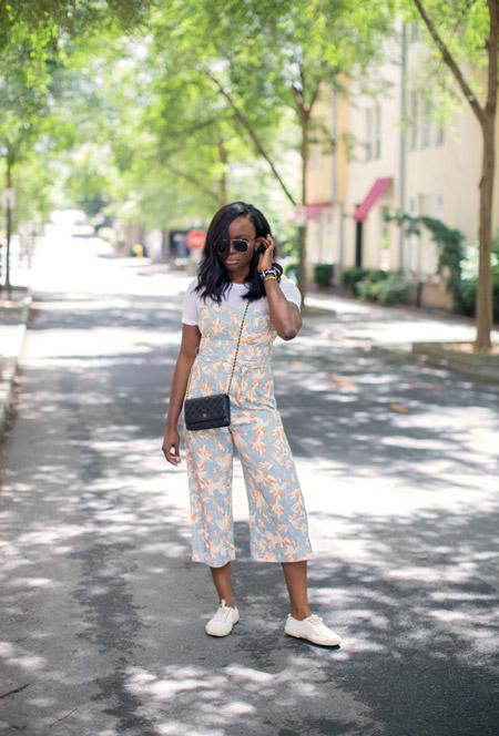 Девушка в комбинезоне пастельных оттенков, мааленькая черная сумочка и кеды