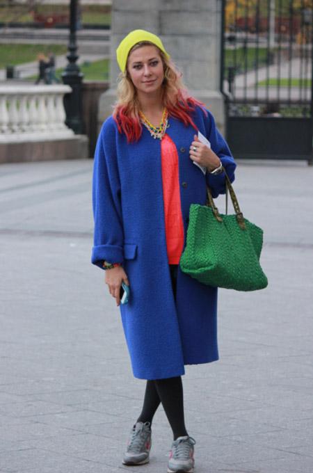 Девушка в коралловом джемпере и синем пальто
