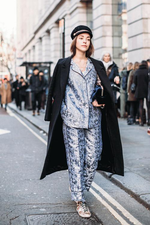 Девушка в костюме в пижамном стиле, кроссовках и черном пальто