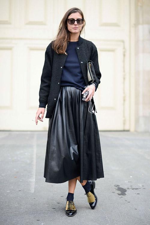 Девушка в кожаной юбке миди, бомбере и черно-золотистых оксфордах