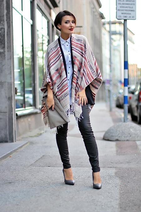 Девушка в кожаных брюках и пончо