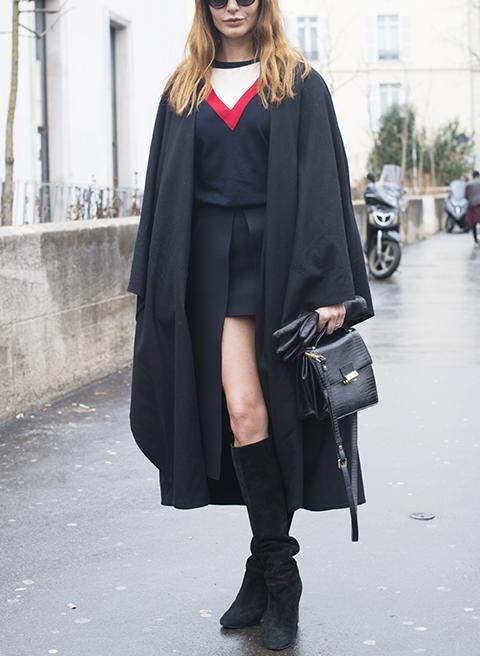 Девушка в мини юбке, черной кофте и черном плаще