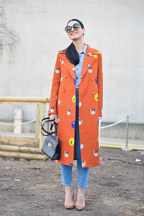 Девушка в оранжевом пальто, укороченных джинсах и кремовых лодочках