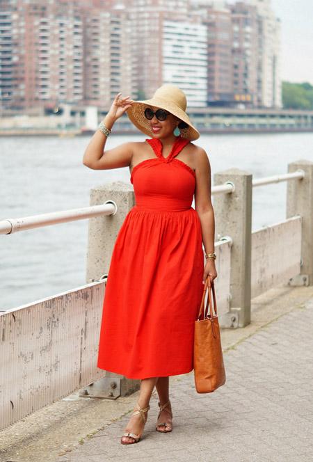 Девушка в оранжевом платье миди, соломенная шляпа и босоножки