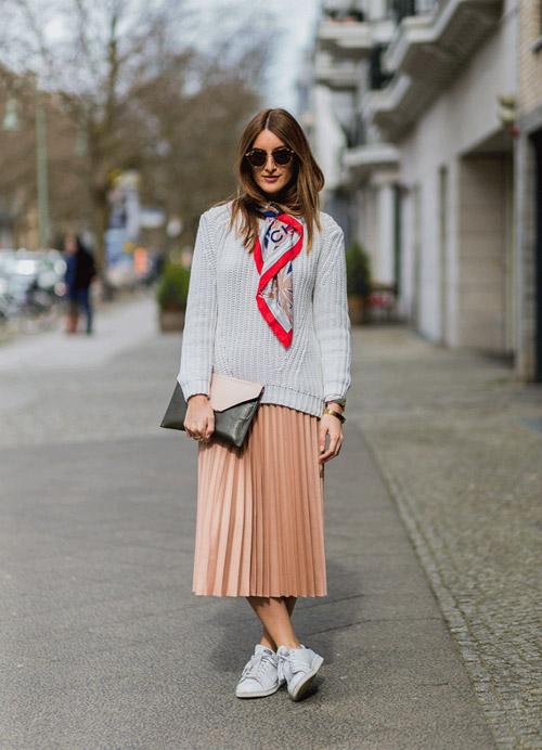 Девушка в плиссированной юбке миди, сером свитере и кроссовках