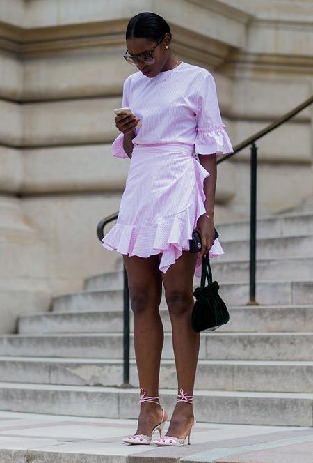 Девушка в розовом платье с воланами, босоножки и маленькая сумочка
