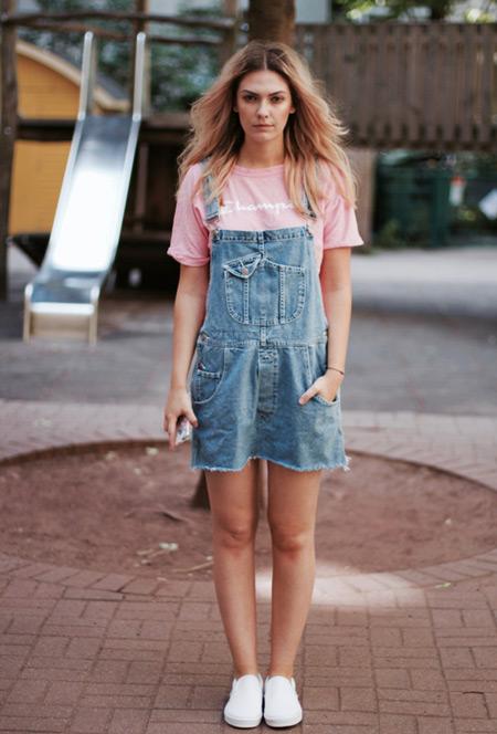 Девушка в розовой футболке, джинсовом сарафане, кеды