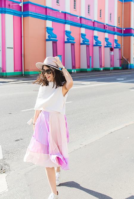 Девушка в розовой плиссированой юбке, белой майке и шляпе