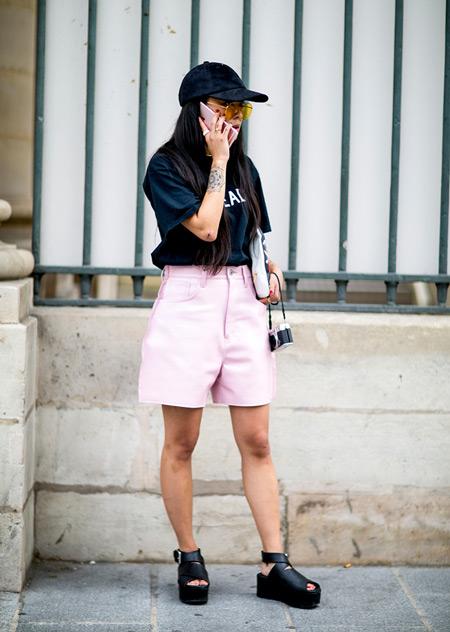 Девушка в розовых шортах бермудах, черная футболка, кепка и босоножки