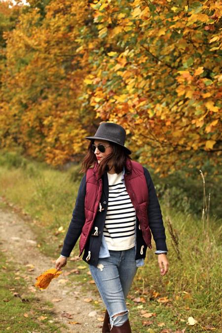 Девушка в рваных джинсах, белом свитшоте, бордовая жилетка и шляпа
