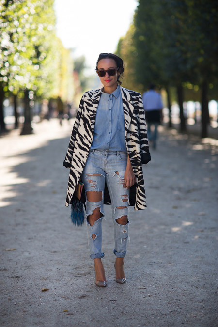 Девушка в рваных джинсах, голубой рубашке и пальто зебра