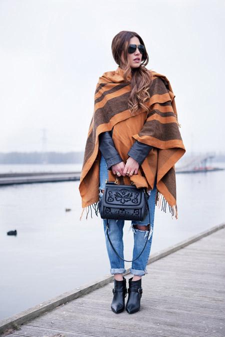 Девушка в рваных джинсах и пончо