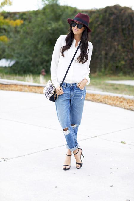 Девушка в рваных джинсах, рубашка, черные босоножки и шляпа