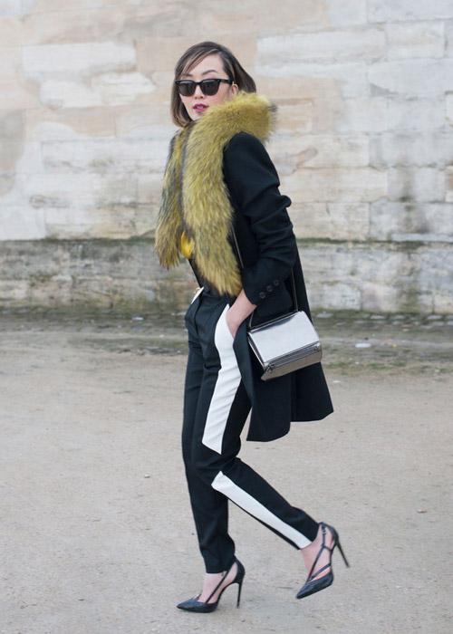 Девушка в спортивных брюках с полоской и пальто с большим меховым воротником