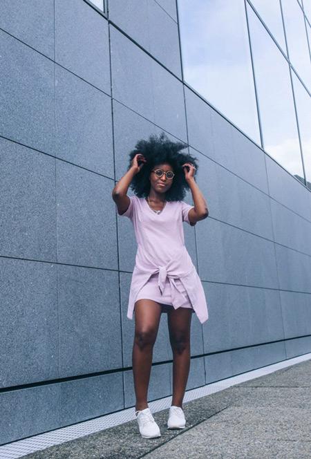 Девушка в светло розовом платье и белых кедах