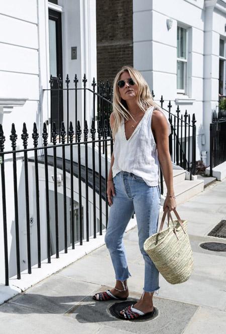 Девушка в укороченных джинсах, белый топ, шлепанцы и соломенная сумка
