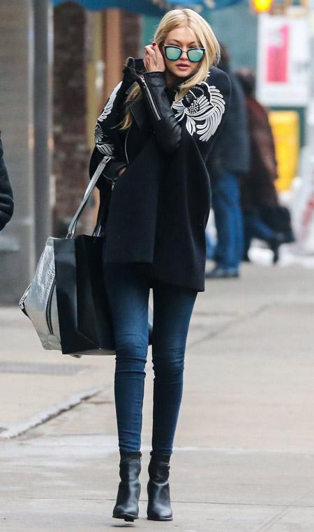 Джиджи Хадид в коротком черном кейпе с рукавами и джинсах