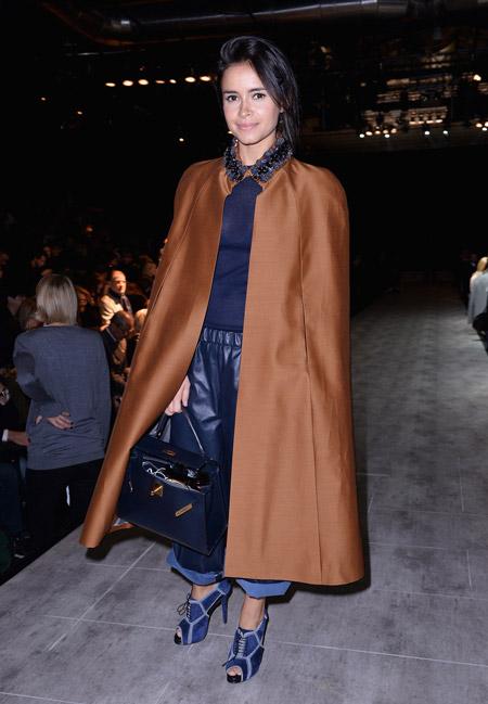 Мирослава Дума в коричневом кейпе накидке, синих штанах и кофте