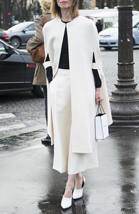 Модель в белых брюках, белая накидка и туфли