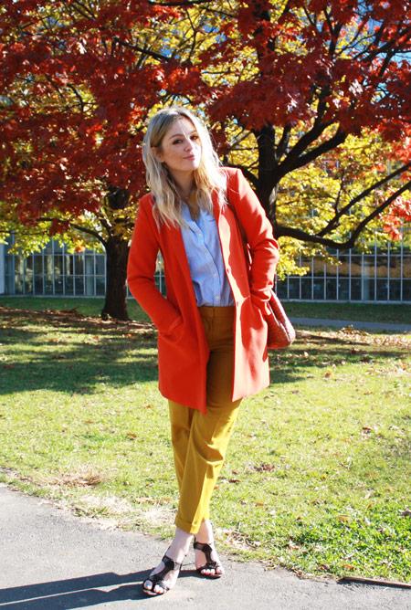 Модель в бриджах горчичного цвета, рубашка и оранжевое пальто