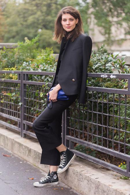 Модель в брюках, черный блейзер и кеды