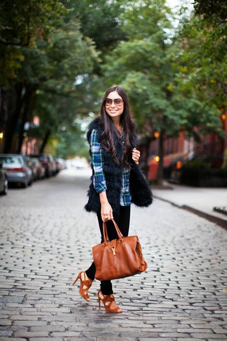Модель в черных штанах, рубашка в клетку, меховой жилет и коричневая сумка и босоножки