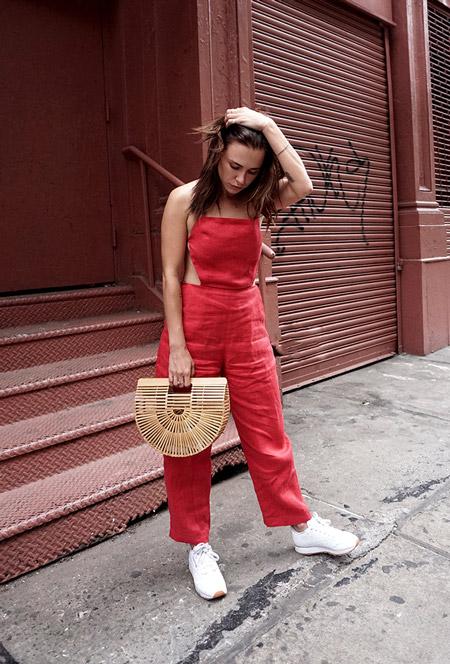 Модель в красном комбинезоне без рукавов и белых кроссовках