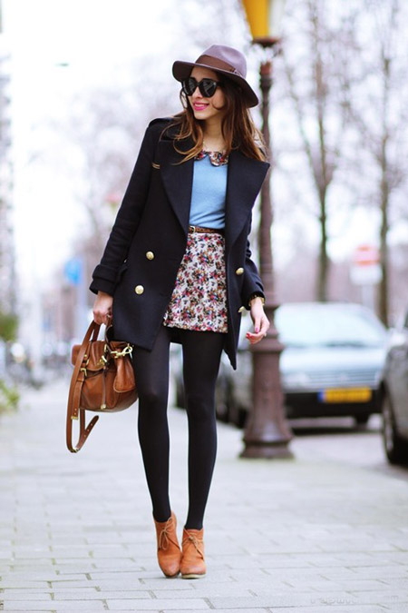 Модель в мини юбке, черное пальто, плотные колготки и шляпа