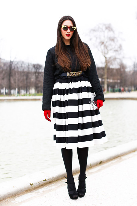 Модель в полосатой черно-белой юбке, черная кофта и красные перчатки