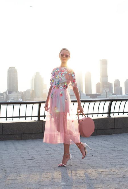 Модель в прозрачном розовом платье расшитое цветами, круглая сумочка и босоножки