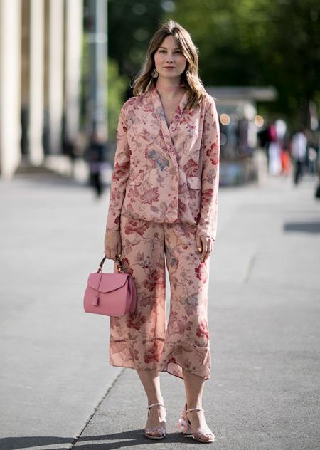 Модель в розовом костюме с цветочным принтом, розовая сумочка и босоножки