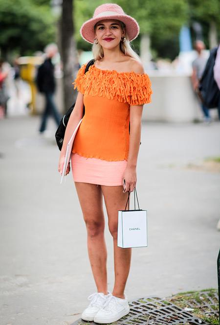 Модель в розовой мини юбке, оранжевая футболка, шляпа и кеды