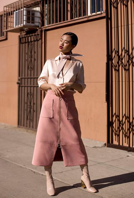Модель в розовой юбке с замком, атласной блузе и сапогах