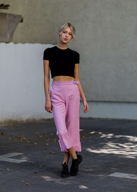 Модель в розовых бриджах и черном кроп топе, кроссовки