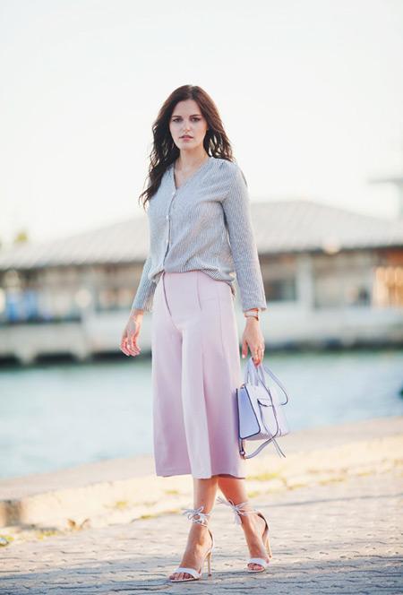 Модель в розовых широких бриджах, кофте и босоножках
