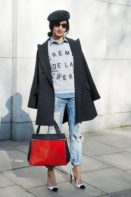 Модель в рваных джинсах, рубашка, черное пальто и кепка