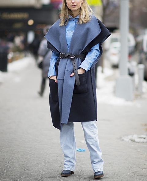 Модель в серой накидке с ремнем и джинсах