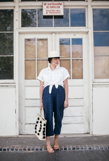 Модель в штанах с высокой талией, белая рубашка, шляпа и сандалии