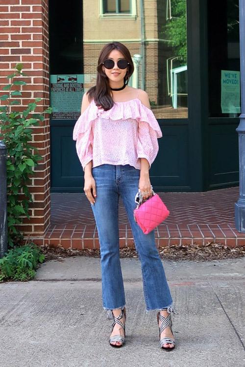 Девушка в розовом топе с открытыми плечами и синих джинсах