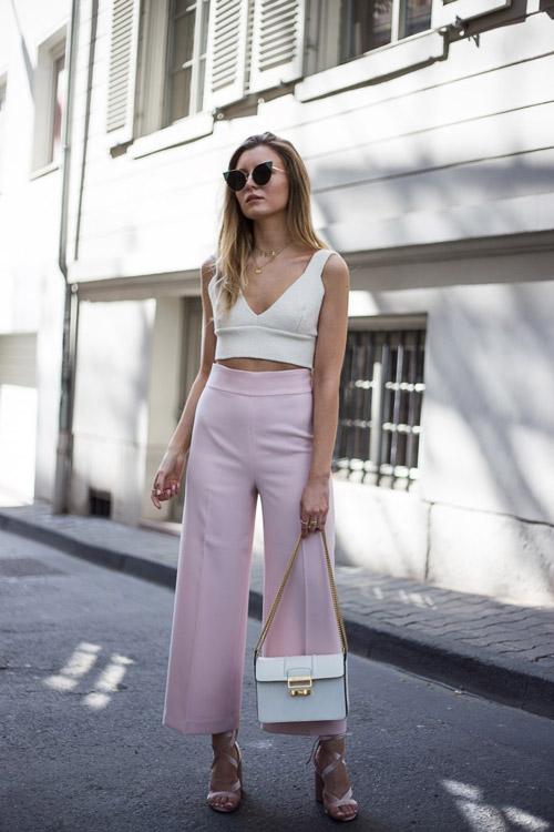 Девушка в розовых брюках, босоножках и белом топе