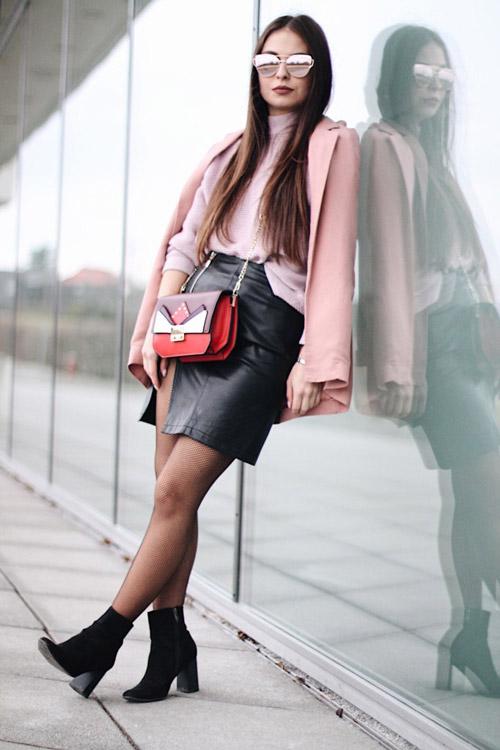 Девушка в черной кожаной мини юбке и розовой водолазке