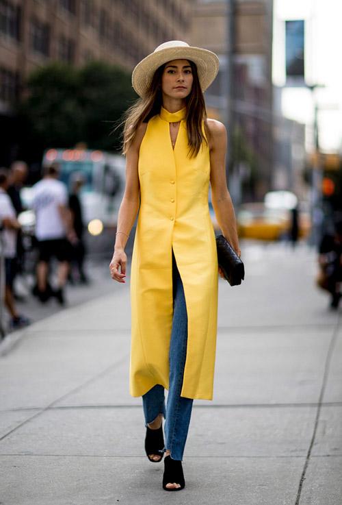 Девушка в желтом длинном жилете, джинсах, черные сабо и шляпа - уличная мода Нью-Йорка весна/лето 2017