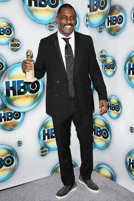 Идрис Эльба в черном костюме и слипонах лабутенах