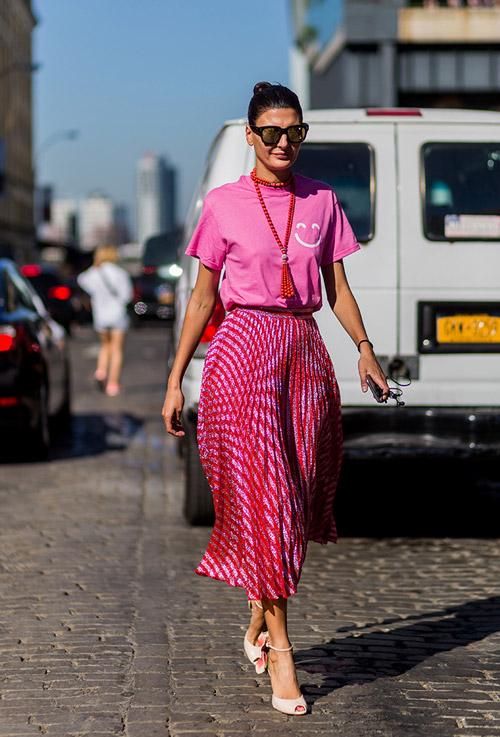 Женщина в плиссированной, розовой юбке миди и розовой футболке - уличная мода Нью-Йорка весна/лето 2017