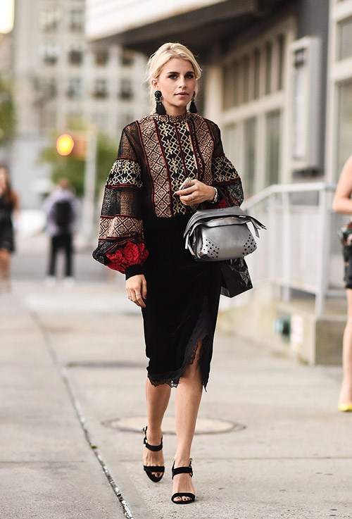 Модель в черной юбке, блузке с узором и черных босоножках - уличная мода Нью-Йорка весна/лето 2017
