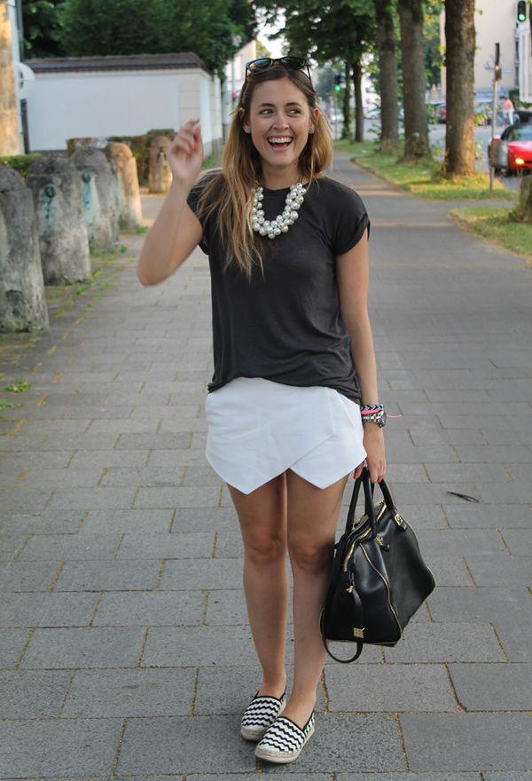 Девушка в белой юбке, черном топе и эспадрильях