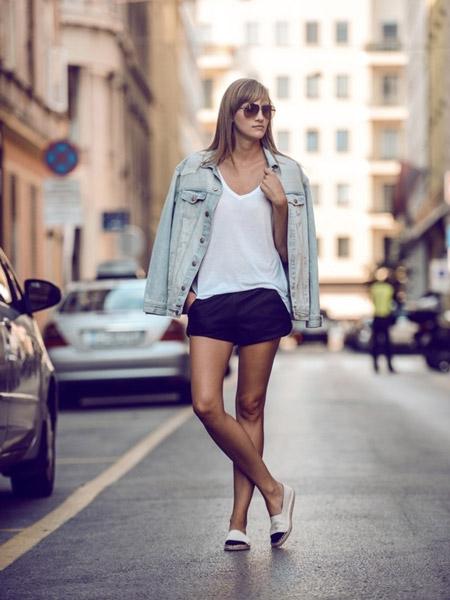Девушка в черных шортах, джинсовке и эспадрильях