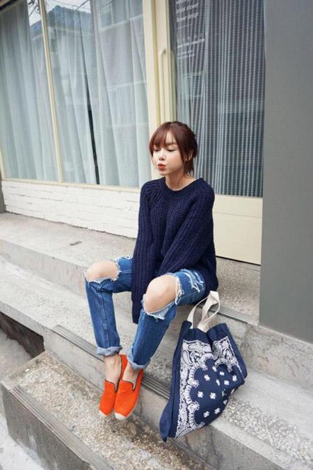 Девушка в рваных джинсах и оранжевых эспадрильях