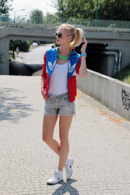 Девушка в белых кроссовках, топе, серых шортах и безрукавке adidas