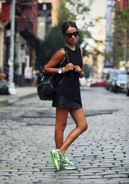 Девушка в черной, кожаной, спортивной юбке, черном топе и кроссовках